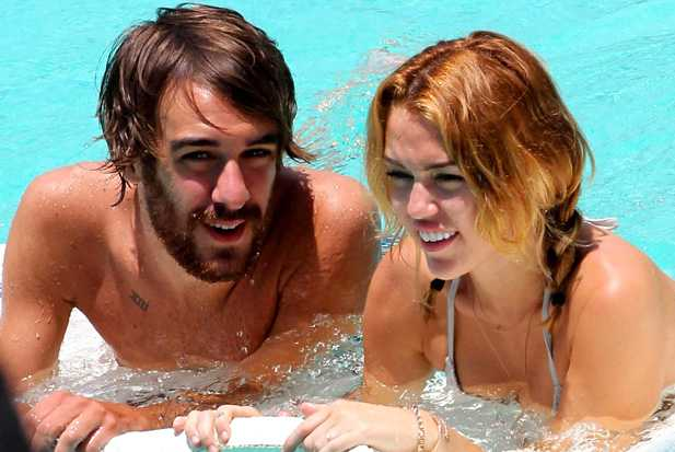 Miley Cyrus and guy in pool - sticky - holding